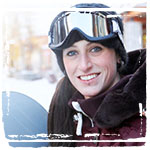 Young woman with snowboard wearing ski goggles, smiling, portrait